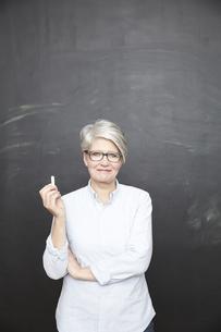 Smiling mature teacher standing at blackboardの写真素材 [FYI04339596]