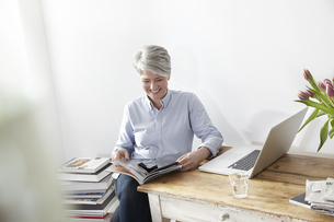 Mature woman sitting at table with magazine and laptopの写真素材 [FYI04339597]