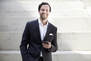Smiling businessman with smartphone in a modern buildingの写真素材 [FYI04339599]