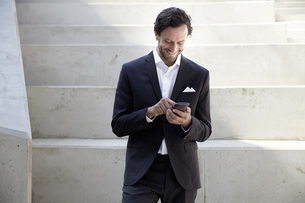 Businessman using smartphone in a modern buildingの写真素材 [FYI04339600]