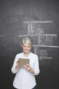 Smiling mature teacher standing at blackboard holding digitaの写真素材 [FYI04339601]
