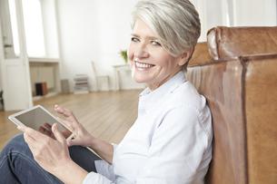 Mature woman sitting on floor using digital tabletの写真素材 [FYI04339602]