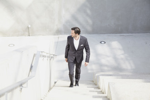 Businessman going upstairs in a modern buildingの写真素材 [FYI04339607]