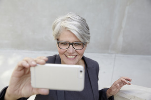 Portrait of smiling career woman taking a selfie with smartpの写真素材 [FYI04339608]