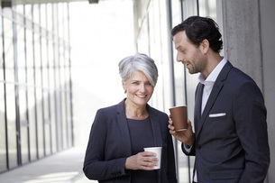 Two smiling business people with coffee to goの写真素材 [FYI04339609]