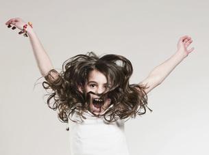Girl (12-13) raising hands and cheering, portraitの写真素材 [FYI04339612]