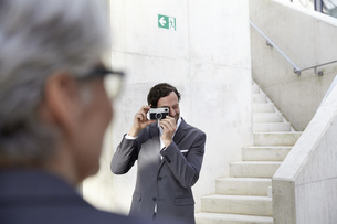 Businessman photographing his female colleague with cameraの写真素材 [FYI04339613]