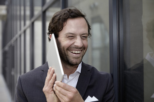 Portrait of laughing businessman trying to phone with his diの写真素材 [FYI04339615]