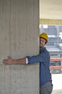 Man with hard hat embracing concrete pillar on constructionの写真素材 [FYI04339623]