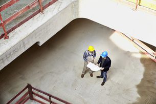 Construction worker and architect with plan talking on constの写真素材 [FYI04339627]