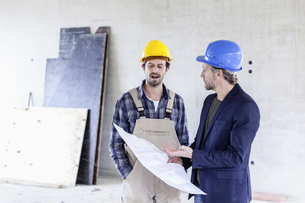 Construction worker and architect with plan talking on constの写真素材 [FYI04339641]