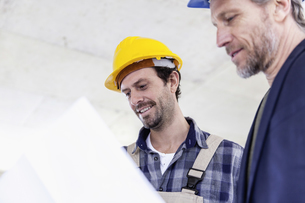 Construction worker and architect with plan talking on constの写真素材 [FYI04339643]