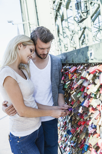Germany, Cologne, young couple looking at love locks on  Hohの写真素材 [FYI04339659]