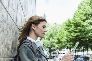 Germany, Cologne, young woman leaning on facade using digitaの写真素材 [FYI04339664]
