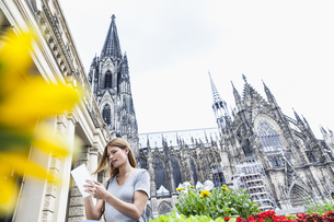 Germany, Cologne, young woman with digital tablet in front oの写真素材 [FYI04339667]