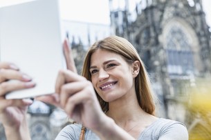 Germany, Cologne, portrait of smiling young woman taking a sの写真素材 [FYI04339668]
