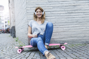 Germany, Cologne, young woman sitting on  pink skateboard heの写真素材 [FYI04339671]