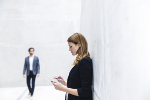 Young businesswoman leaning on concrete wall using digital tの写真素材 [FYI04339672]