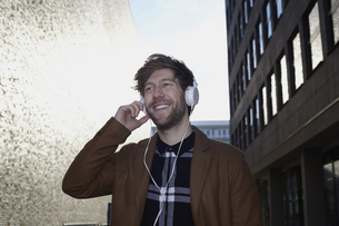 Smiling young man listening music with headphones at backligの写真素材 [FYI04339734]