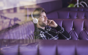 Young man sitting in a lounge bar hearing music with headphoの写真素材 [FYI04339735]