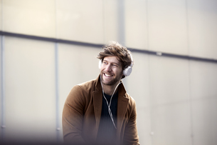 Smiling young man listening music with headphones at backligの写真素材 [FYI04339743]