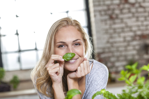 Portait of smiling blond woman holding basil leafの写真素材 [FYI04339745]