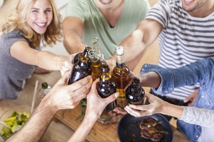 Friends clinking beer bottles in kitchenの写真素材 [FYI04339748]