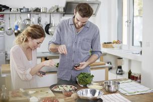 Couple preparing pizza in kitchenの写真素材 [FYI04339754]