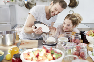 Couple in kitchen pouring sugar into bowlの写真素材 [FYI04339757]