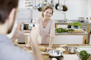 Man taking cell phone picture of smiling woman preparing douの写真素材 [FYI04339761]
