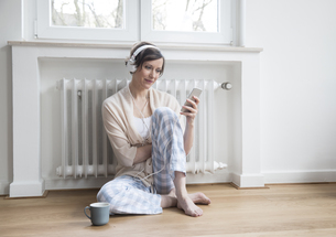 Woman at home sitting on floor with cell phone and headphoneの写真素材 [FYI04339762]