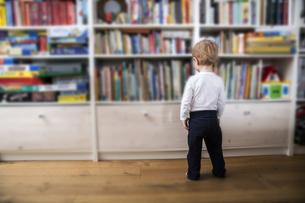 Little boy standing in front of book shelfの写真素材 [FYI04339784]