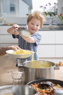 Proud little boy serving pasta in kitchenの写真素材 [FYI04339785]