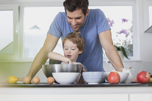 Father and son preparing waffle dough in kitchenの写真素材 [FYI04339801]