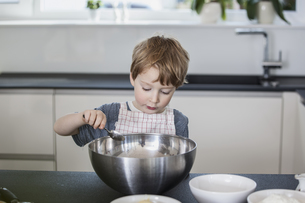 Little boy helping to prepare food in the kitchenの写真素材 [FYI04339802]