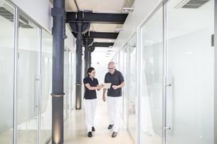 Two dentists using digital tablet in corridorの写真素材 [FYI04339808]