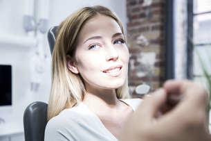 Young woman at the dentist receiving treatmentの写真素材 [FYI04339812]