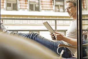 Man sitting on balcony using digital tabletの写真素材 [FYI04339818]