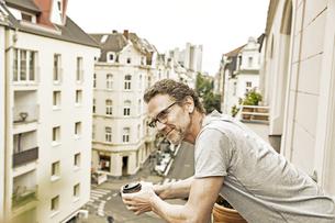 Smiling man on balcony looking downの写真素材 [FYI04339819]
