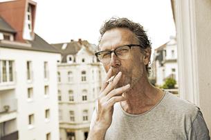 Portrait of man smoking on balconyの写真素材 [FYI04339820]