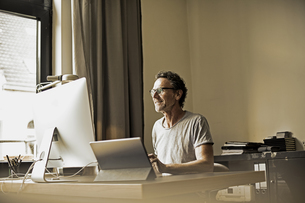 Man sitting at desk working with computerの写真素材 [FYI04339821]