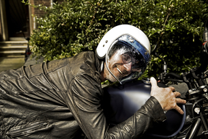 Smiling man wearing motorcycle helmet and leather jacket lyiの写真素材 [FYI04339826]
