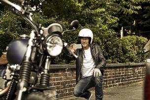 Smiling man with motorcycle helmet taking photo of his motorの写真素材 [FYI04339827]