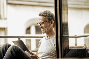 Smiling man sitting on balcony using digital tabletの写真素材 [FYI04339830]