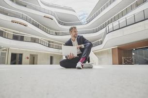 Businesssman sitting on floor in office building using laptoの写真素材 [FYI04339849]