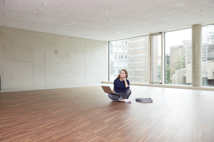Young woman using laptop in empty roomの写真素材 [FYI04339864]