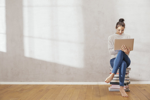 Young woman sitting on stack of books using laptop at homeの写真素材 [FYI04339880]