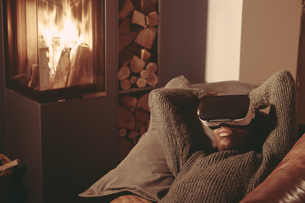 Young man with Virtual Reality Glasses lying on the couch atの写真素材 [FYI04339881]