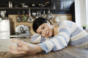 Woman in kitchen resting on table holding cell phoneの写真素材 [FYI04339894]