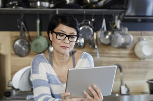 Woman in kitchen looking on tabletの写真素材 [FYI04339895]